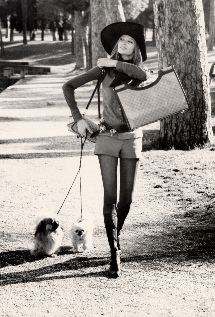 ca. 1971, Rome, Italy --- Russian model, Veruschka, walking with two dogs in the Borghese Gardens of Rome, wearing a light suede vest and short shorts with a dark shirt and leather belts by Gucci, a wide-brimmed black straw hat by Remo Argenti, and knee-high black leather boots by Mario Valentino, and holding a large shoulder bag and travel bag by Gucci. --- Image by © CondÈ Nast Archive/CORBIS